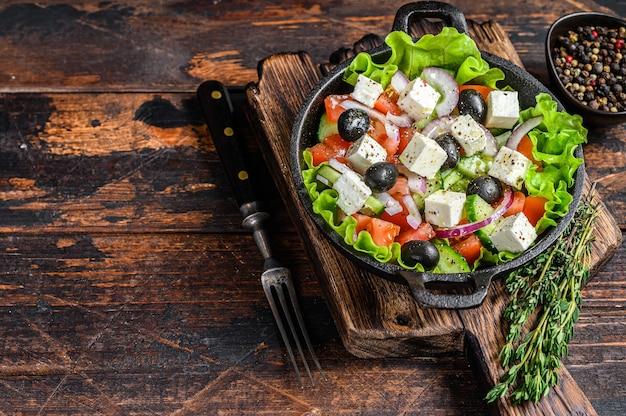 Griekse salade met verse groenten en fetakaas in een pan. donkere houten tafel. bovenaanzicht. kopieer ruimte.