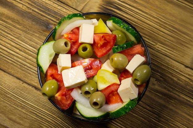 Griekse salade met verse groenten, fetakaas en groene olijven in glazen kom op houten tafel
