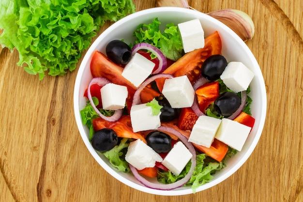 Griekse salade met verse groenten, fetakaas en zwarte olijven op een houten achtergrond.
