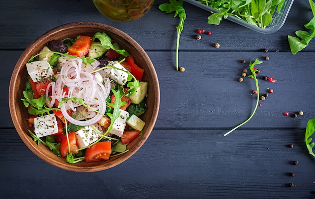 Griekse salade met verse tomaat, komkommer, rode ui, basilicum, fetakaas, zwarte olijven en italiaanse kruiden. bovenaanzicht