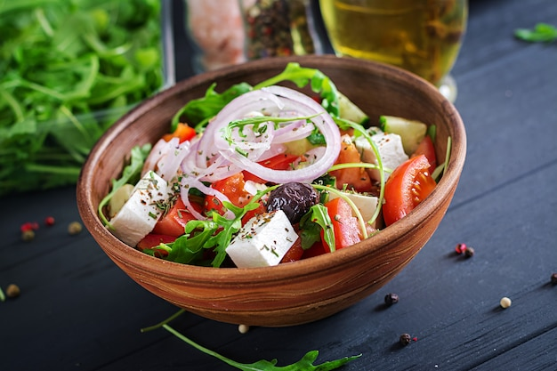Griekse salade met verse tomaat, komkommer, rode ui, basilicum, fetakaas, zwarte olijven en italiaanse kruiden