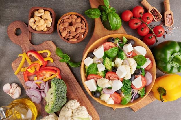 Griekse salade of horiatiki met grote stukjes tomaten, komkommers, ui, fetakaas en olijven in witte kom geïsoleerd bovenaanzicht. dorpssalade met blokjes mozzarella, rucola, peterselie en olijfolie