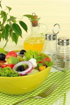 Griekse salade op bord op tafel op tafelkleed