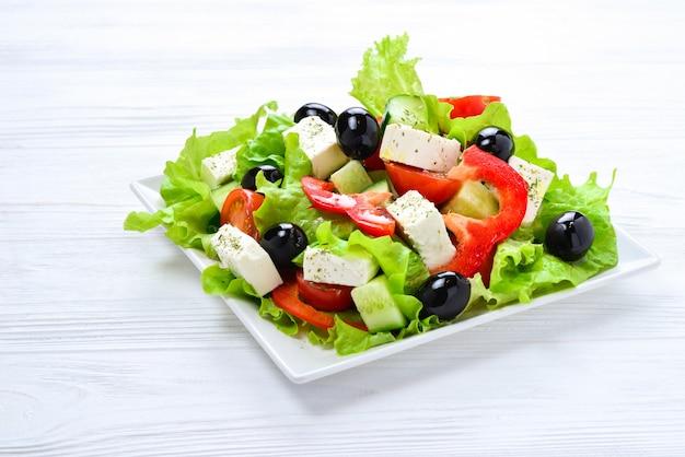 Griekse salade op een witte houten achtergrond. ruimte voor tekst of ontwerp.