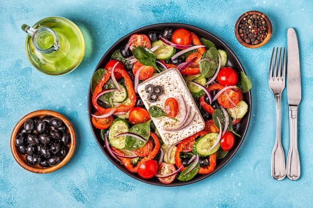 Griekse salade van verse komkommer, tomaat, paprika, spinazie, rode ui, fetakaas en olijven