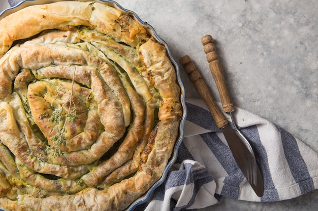 Griekse taart spanakopita over concrete achtergrond. ideeën en recepten voor vegetarische of veganistische spinazietaart van fillogebak in plakjes gesneden