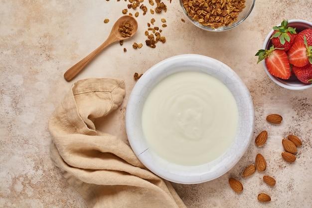 Griekse yoghurt in witte kom met ingrediënten voor het maken van ontbijtgranola en verse aardbeien op oude beige lijst. bovenaanzicht.