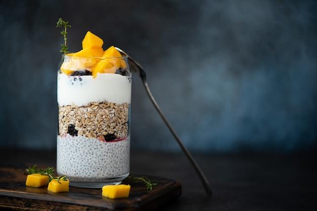 Griekse yoghurt met havermout, chiazaad en mango op een glazen pot