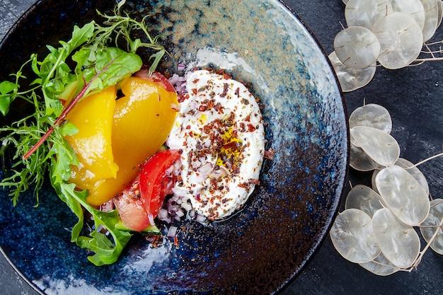 Griekse yoghurt met olijfolie, kruiden met gebakken groenten, paprika en tomaat in donkere kom. gezond, veganistisch eten voor een dieetmenu. eten foto achtergrond