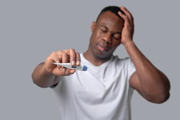 Griep. een man met een donkere huidskleur in een wit t-shirt die zich onwel voelt