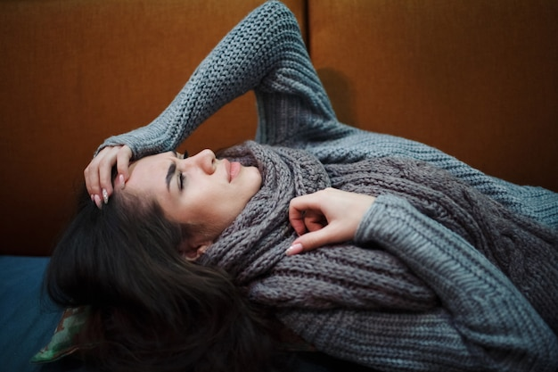 Griep koud symptoom. zieke jonge vrouw met koorts die in weefsel niest, allergieën, verkoudheid die op het bed met sjaal legt.