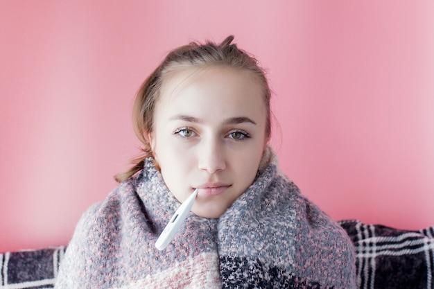 Griep koude grippe. vrouw die op hoge temperatuur heeft. ziek meisje dat met koorts kwikthermometer controleert op roze achtergrond.