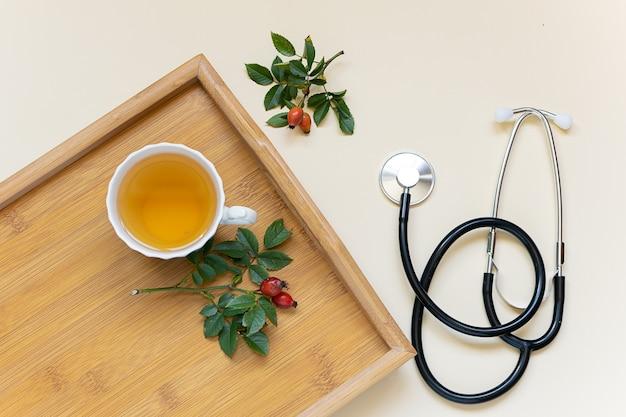 Griepseizoen concept. kopje kruidenvitaminethee op het houten dienblad en de medische stethoscoop.