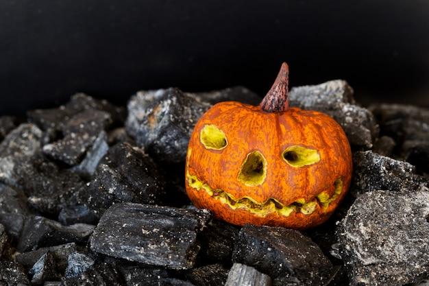 Griezelig model van halloween-pompoen op donkere houtskool. close-up, selectieve aandacht