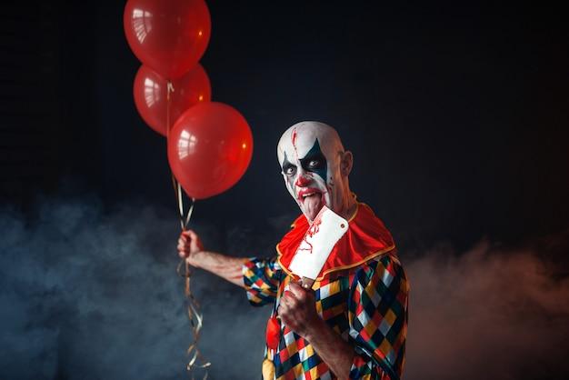 Griezelige bloedige clown met mes houdt luchtballonnen vast, horror. man met make-up in carnavalskostuum, gekke maniak