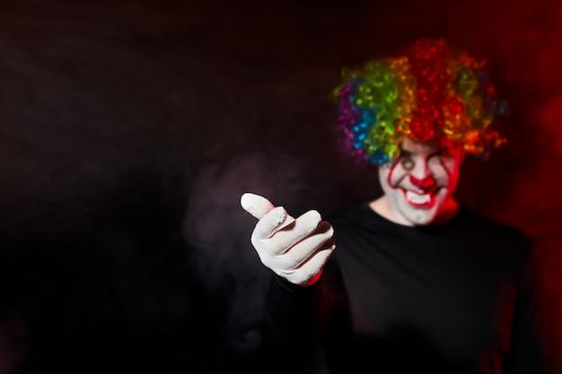 Griezelige clown in een gekleurde pruik glimlacht en wenkt aan zichzelf met een gebaar van zijn hand.