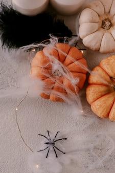 Griezelige halloween-decoratie met verschillende pompoenen, licht, spinnen.