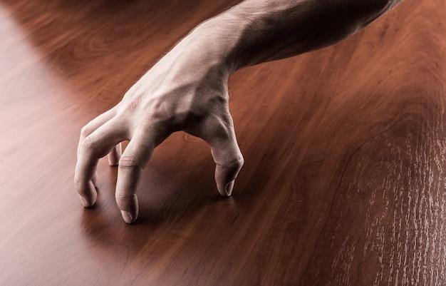 Griezelige hand op de houten tafel Premium Foto