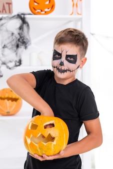 Griezelige jonge jongen met kwade halloween-pompoen