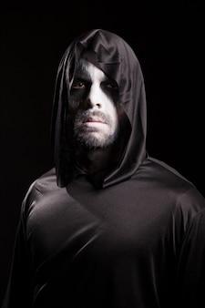 Griezelige man verkleed als magere hein voor halloween.