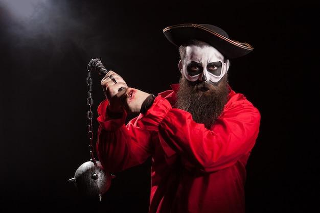 Griezelige mannelijke piraat met lange baard die een foelie over zwarte achtergrond houdt. halloween-outfit.