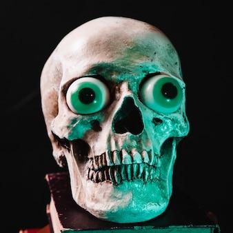 Griezelige schedel met speelgoed ogen op boek