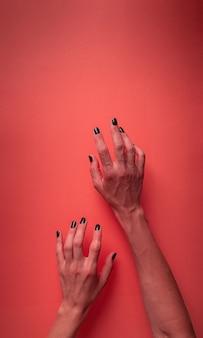 Griezelige vrouw halloween handen met zwarte nagels op rode bloedige achtergrond