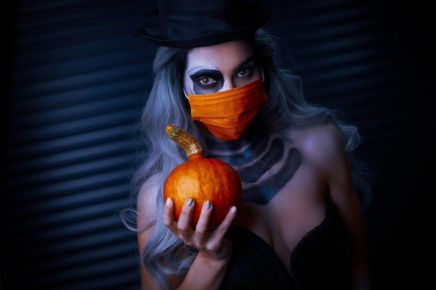 Griezelige vrouw in halloween-gotische make-up die gezichtsmasker draagt vanwege covid-19-beperkingen