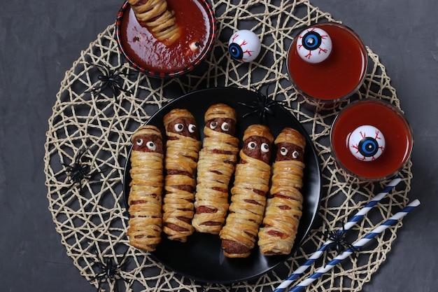 Griezelige worstmummies, tomatensap en saus voor halloween-feest op zwart. bovenaanzicht.