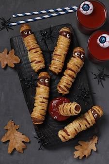 Griezelige worstmummies, tomatensap en saus voor halloween-feest op zwarte houten bord. bovenaanzicht