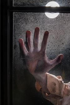 Griezelige zombiehand op een raam