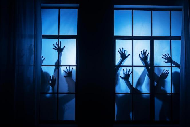 Griezelige zombiehanden op een raam