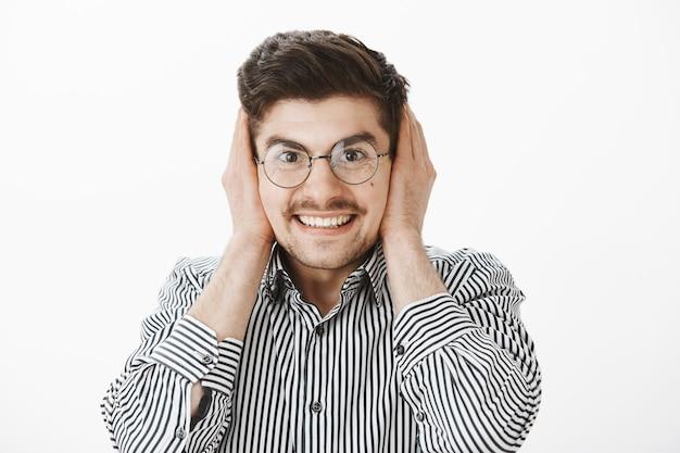 Grijnzend opgewonden aantrekkelijk mannetje met bril, oren bedekt met handpalmen en breed glimlachend, wachtend op hard geluid van vuurwerk of knal, blij en blij tijdens feest over grijze muur