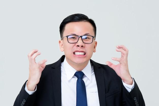 Grijnzende aziatische zakenman die boos met handen het drukken voelen