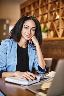 Grijp het moment dat jonge, mooie zakenvrouw glimlacht terwijl ze in een notitieboekje schrijft terwijl ze in café werkt