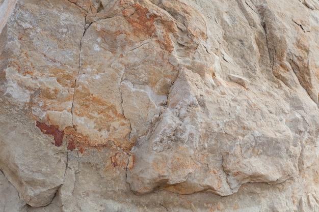 Grijs-beige steen textuur. rots. stenen achtergrond. reliëfoppervlak. prachtig natuurlijk patroon op het vliegtuig. rasterafbeelding.