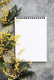 Grijs bureau met geel mimosabloemenboeket en schoon notitieboekje, flatlay