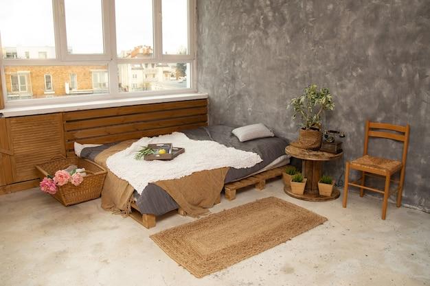 Grijs en goud, modern slaapkamerinterieur met kingsize bed versierd met kussens en dekens