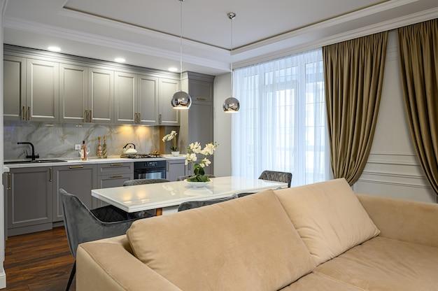 Grijs en wit eigentijds klassiek keukeninterieur ontworpen in moderne stijl als onderdeel van een studio-appartement