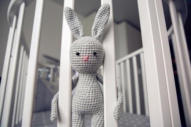 Grijs gebreid konijn achter de scheidingswanden in bed