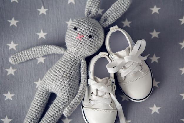 Grijs gebreid speelgoedkonijn en witte kinderschoentjes