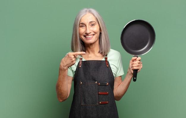 Grijs haar de vrij vrouw van de middelbare leeftijdschef-kok met een pan
