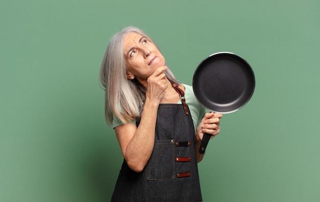Grijs haar mooie middelbare leeftijd chef-kok vrouw met een pan