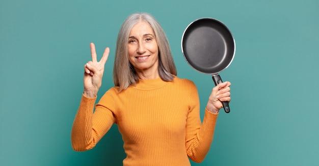 Grijs haar vrij middelbare leeftijdsvrouw die kok met een pan leert