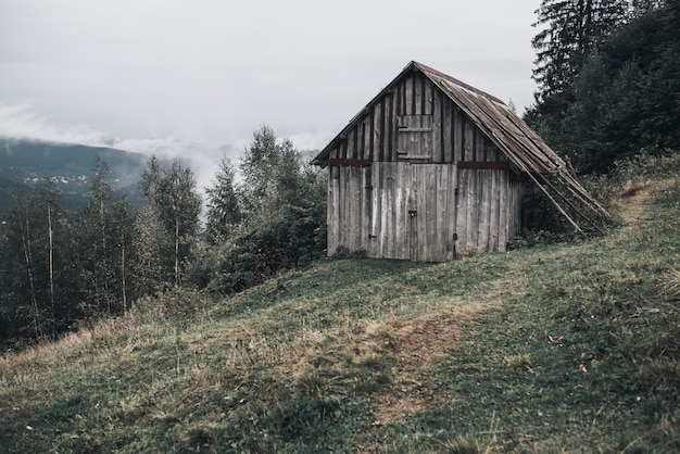 Grijs houten huis met planken in de karpaten. yaremche. mist over het bos.
