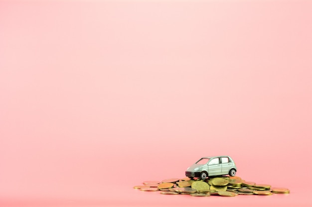 Grijs miniatuurautomodel en gouden muntstukkenstapel op roze achtergrond.