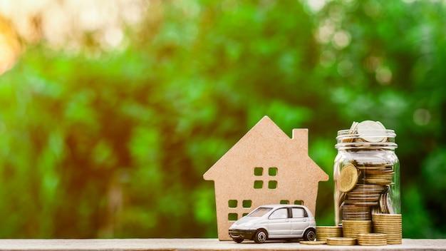 Grijs miniatuurautomodel en muntstukken op houten lijst.
