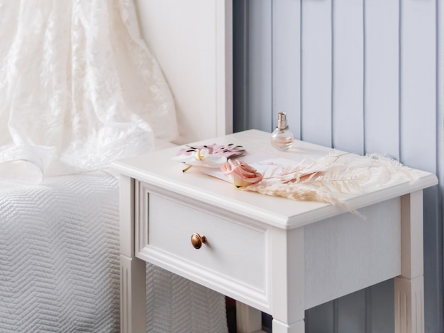 Grijs nachtkastje met bruidsaccessoires. decoratieve monsterabladeren en pampagras, lichtroze roze bloemen en een fles parfum.