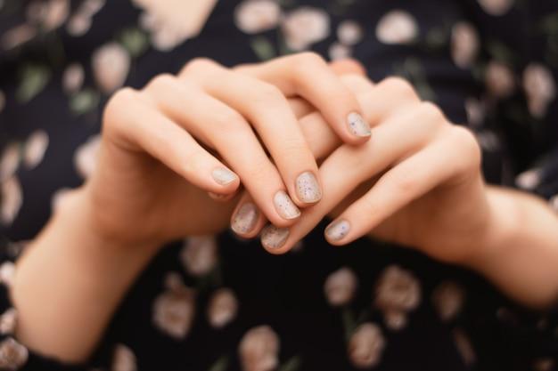 Grijs nageldesign. vrouwelijke hand met glitter manicure.