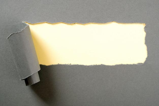 Grijs papier gescheurde gescheurde strip gele achtergrond
